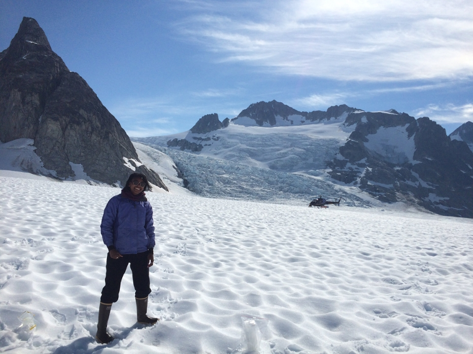 a woman stands on snow in front of mountains and glaciers