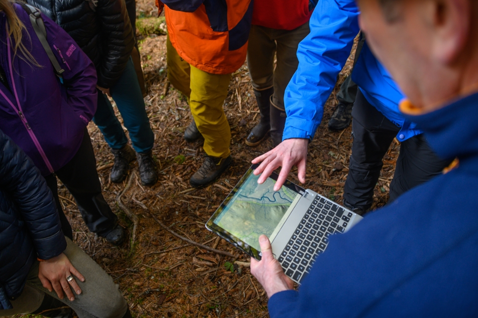 researchers analyze stream samples on a river bank